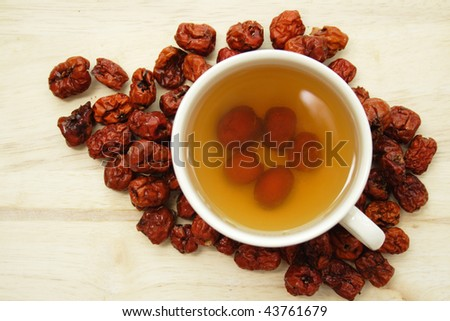 A cup of Chinese red date tea with pitted dates around the cup, taken from top angle - stock photo