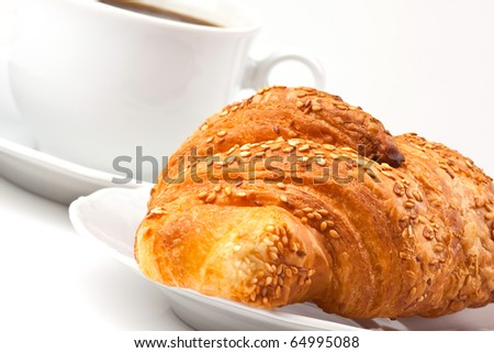 A cup of coffee and a croissant with sesame seeds - stock photo