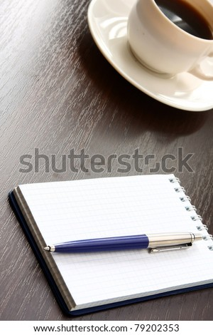 A cup of coffee and a notebook with a pen on a wooden table - stock photo