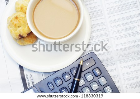 a cup of coffee and calculator  on newspaper