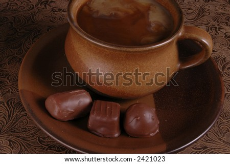 A cup of coffee and chocolate candy against a warm, brown background.