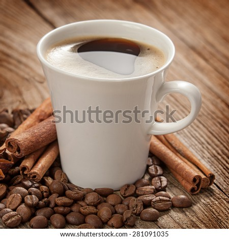A cup of coffee and cinnamon sticks on the old board. - stock photo