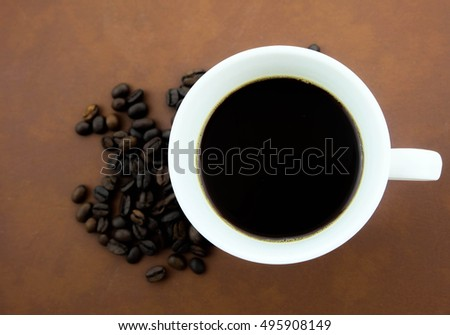 A cup of coffee and coffee beans. Brown background.
