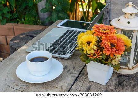 a cup of coffee and laptop on wood floor with flower - stock photo