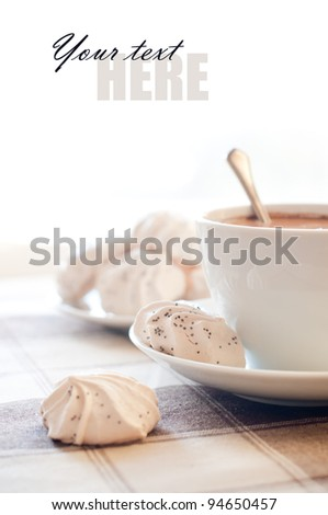 A cup of coffee and meringues in the bright morning sunlight
