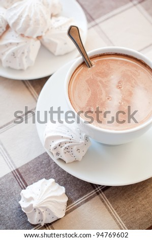 A cup of coffee and meringues on brown cloth - stock photo