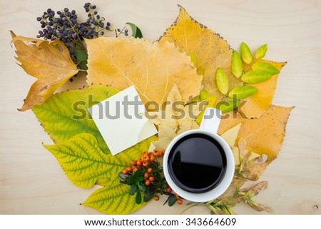 A cup of coffee and note with bouquet of yellow, green autumn leaves,berries and seeds. - stock photo