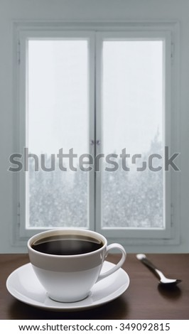 A cup of coffee and snowstorm view from the window on the background - stock photo