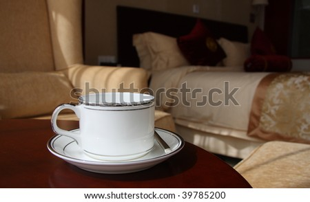 a cup of coffee and spoon at the table in the hotel room. - stock photo
