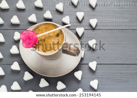 A cup of coffee and sweets: a heart shaped lollipop and sugar cubes - stock photo