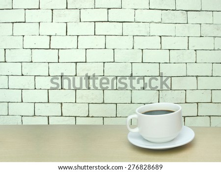 a cup of coffee and white brick wall background with copy space for text - stock photo