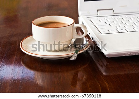 A cup of coffee beside white notebook - stock photo