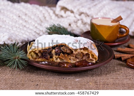 A cup of coffee, cinnamon, cake, knitted scarf - winter still life