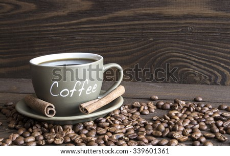 A cup of coffee, coffee beans and cinnamon sticks bark lying on an old wooden table