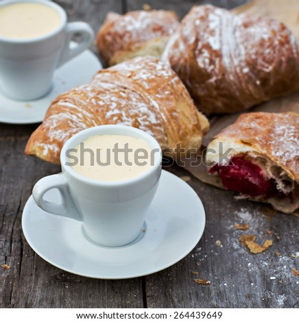 "A cup of coffee ""espresso"" and croissant on the wooden table."