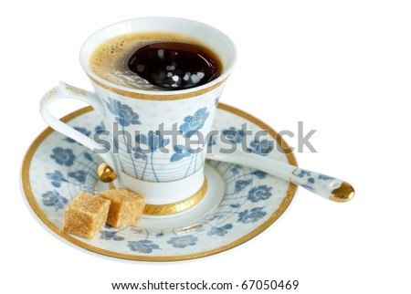 A cup of coffee from fine porcelain with two pieces of cane lump sugar  on a saucer