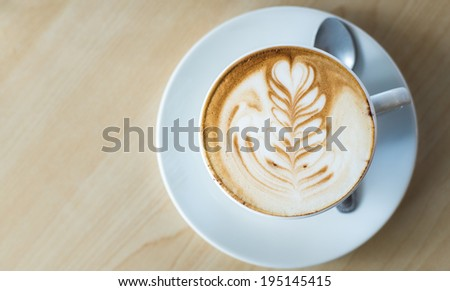 A cup of coffee in a white cup on wooden background - stock photo