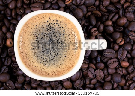 A cup of coffee is on the background of roasted coffee beans - stock photo