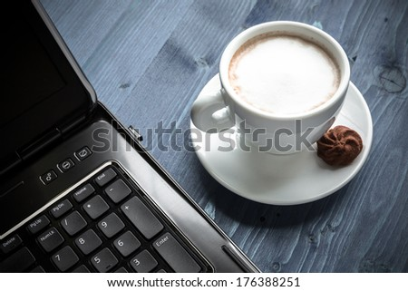 a cup of coffee, laptop - stock photo