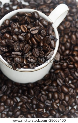 A cup of coffee, made from the coffee bean.  This is a graphical representation of coffee and the pleasure it brings people - stock photo