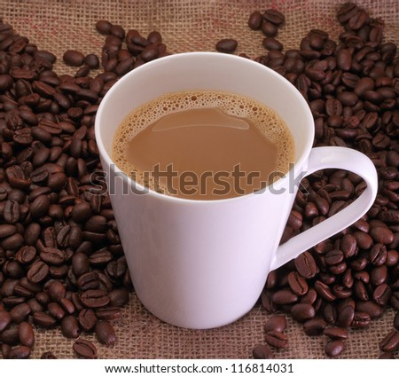 A cup of coffee milk and coffee beans on sack burlap background. - stock photo