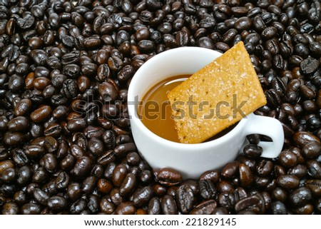 A cup of coffee milk arranged with raw coffee bean and coffee cake - stock photo