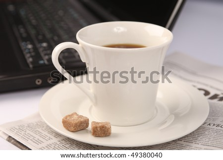 a cup of coffee newspaper and laptop - stock photo