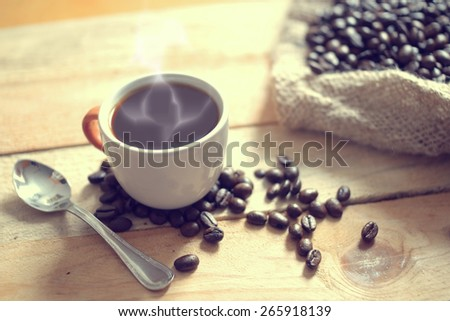 A cup of coffee next to some fresh roasted coffee beans on a burlap sack, next to a window in a rustic kitchen. - stock photo