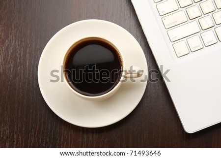 A cup of coffee on a laptop