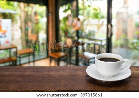 A Cup of coffee  on a rustic wooden table with coffee shop blurred background. - stock photo