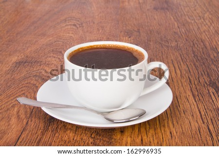 A cup of coffee on a wooden background - stock photo