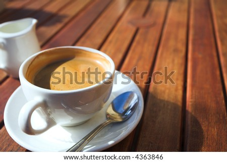 A cup of coffee on a wooden table in an outdoor cafe. Shallow depth of field, focus on the rim of the cup - stock photo