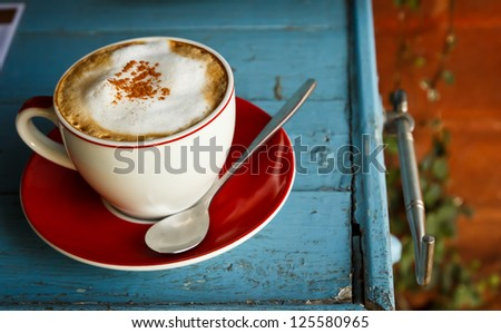a cup of coffee on blue wood - stock photo