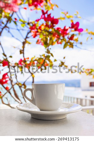 A cup of coffee on table with Italian town at the background - stock photo