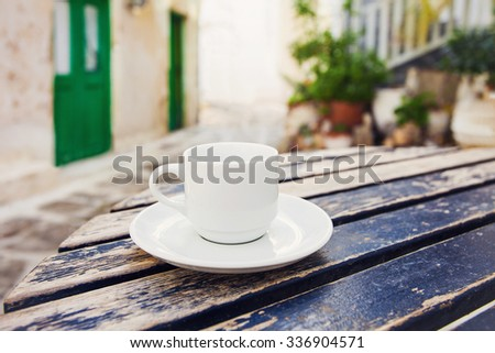 A cup of coffee on table with Mediterranean town at the background - stock photo