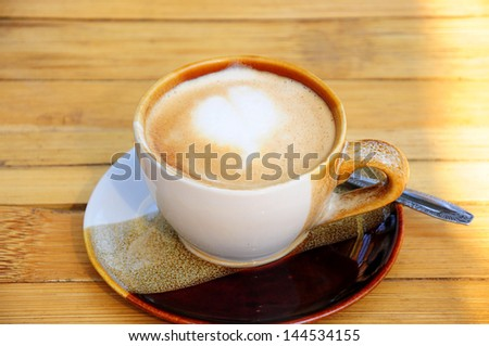 A cup of coffee on the wooden background - stock photo