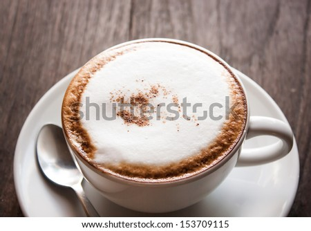 a cup of coffee on the wooden floor or table - stock photo