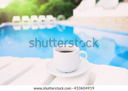 A cup of coffee over a swimming pool, vacations concept - stock photo