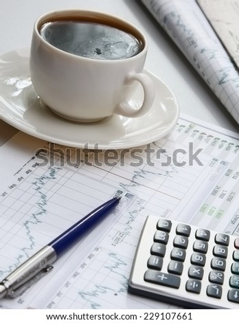 A cup of coffee, paper and a pen on a laptop. - stock photo