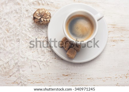 A cup of coffee, snowflake on white wooden background, selective focus - stock photo
