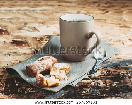A Cup of coffee ,sugars and metal spoon, biscuits sprinkled with sugar on a napkin on a wooden table. - stock photo