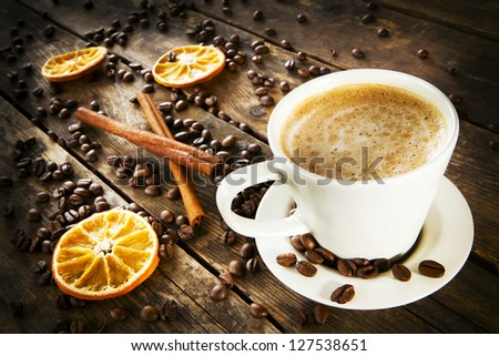 A cup of coffee surrounded by coffee beans and orange slices.