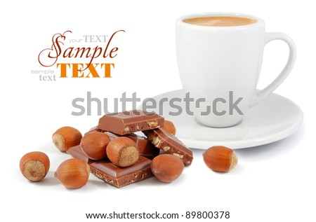 A cup of coffee with a chocolate and nuts on a white background - stock photo