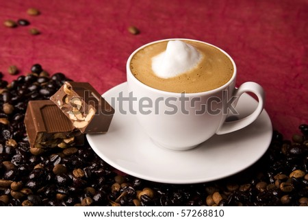 A cup of coffee with chocolate and coffee beans. Copy space. Selective focus in the center of the drink.