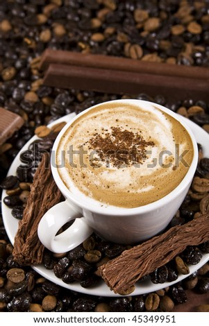 A cup of coffee with chocolate and coffee beans. Selective focus in the center of the drink. - stock photo