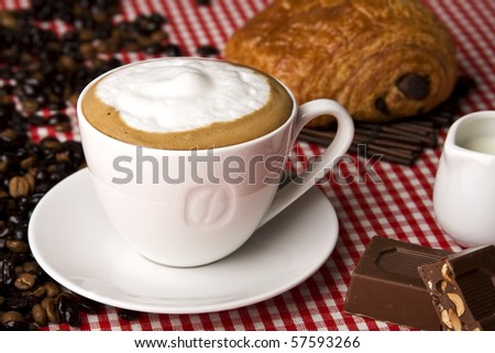 A cup of coffee with chocolate, coffee beans and milk jug. Copy space. Selective focus in the center of the drink. - stock photo
