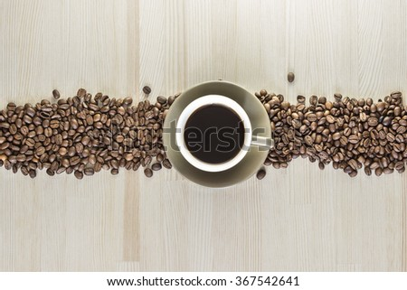 A cup of coffee with coffee beans on a wooden table. - stock photo