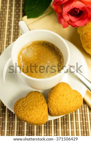 a cup of coffee with cookies shaped like a heart - stock photo