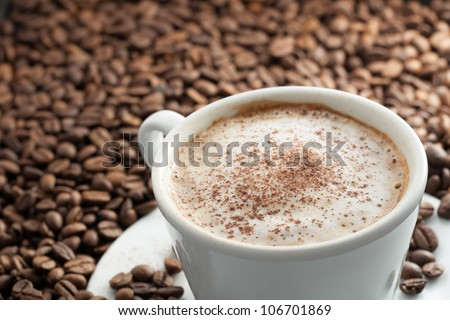A Cup of Coffee with Foam and Cinnamon on top of Coffee Beans with Scattered Beans on Plate - stock photo