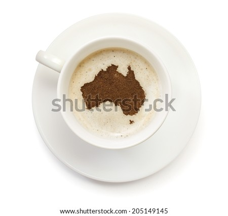 A cup of coffee with foam and powder in the shape of Australia.(series) - stock photo